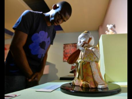 "Renardo Reid browses the various dolls in the Kimekomi Ningyo ""Wooden dolls dressed in kimono"" display section of the Dolls of Japan exhibition at the National Museum. In the foreground stands the  ""Shirabe: Melody"" doll a figure of a young girl in ancient costume who is about to play the Biwa, a four-stringed Japanese lute."
