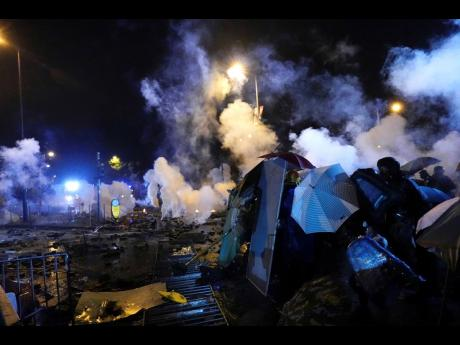 Protesters react as police fire tear gas near Hong Kong Polytechnic University after they gave protesters an ultimatum to leave the campus in Hong Kong, on Sunday, November 17, 2019. Police launched a late-night operation Sunday to try to flush about 200 protesters out of a university campus on a day of clashes in which an officer was hit in the leg with an arrow and massive barrages of tear gas and water cannons were fired.